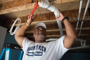 a man working on a house's plumbing