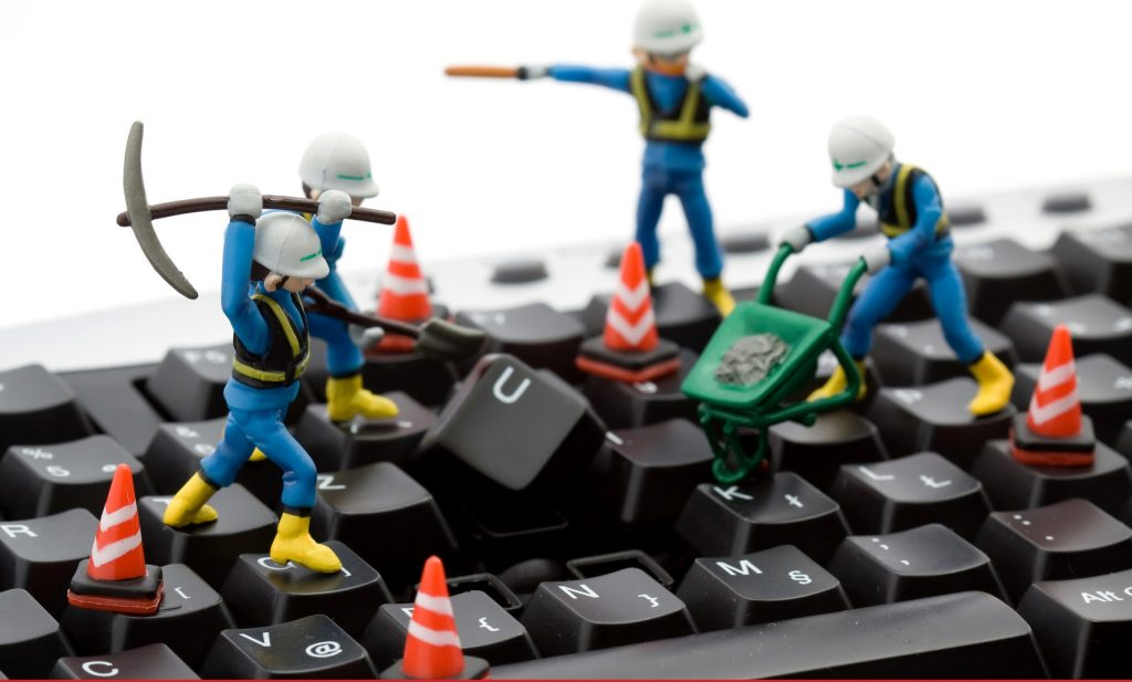 toy construction workers fixing a keyboard