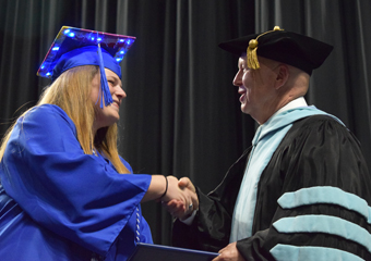 a graduate shaking Dr. Green's hand