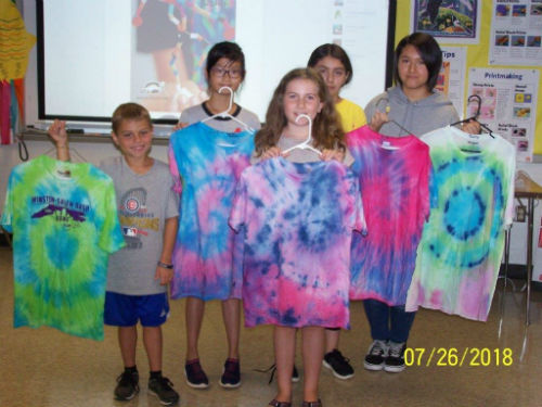 kids holding their tie dye shirts