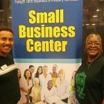 Alan and a lady standing next to a Small Business Center sign