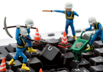 toy construction workers working on a computer