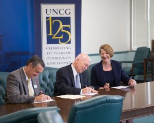 Signing the UNCG and Forsyth Tech co-admission agreement are Dr. Joel Welch, vice president of instructional services, Forsyth Tech; Dr. Gary Green, president of Forsyth Tech; and Dr. Dana Dunn, provost and senior vice chancellor, UNCG.