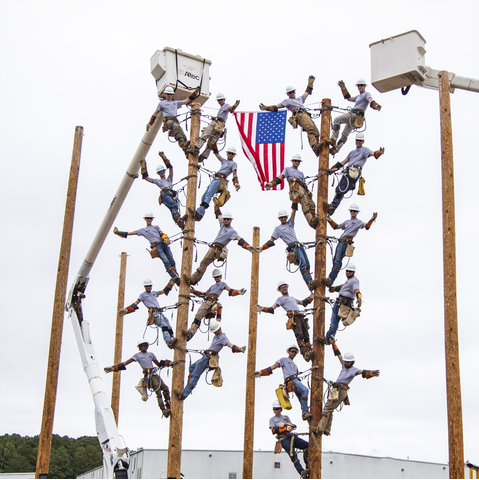 All 21 Forsyth Tech linemen graduates on the poles waving to family members