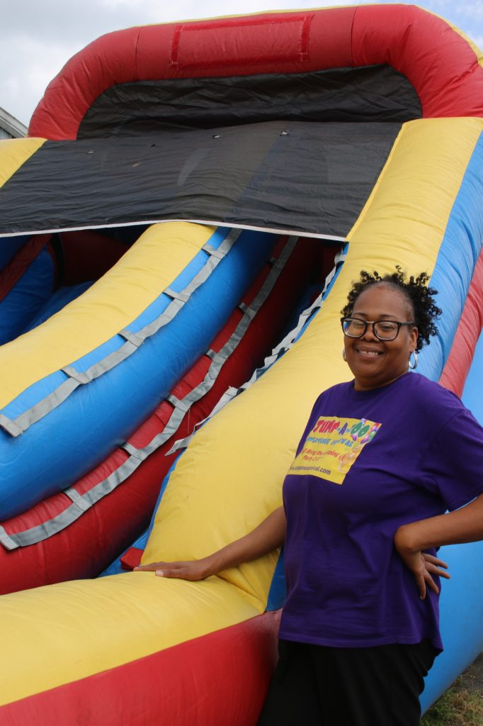 Juvonne Johnson standing next to a bouncy castle slide