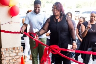 Reanee B. McManus cutting a red ribbon with scissors
